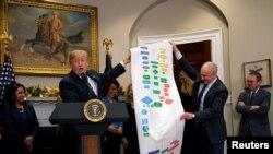 Para graficar lo engorroso de algunas regulaciones federales, el presidente Trump junto al asistente del presidente para iniciativas estratégicas, Chris Liddell muestran en cuadros el proceso que involucró construir una autopista federal.