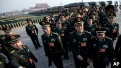 FILE - Delegates from Chinese People's Liberation Army line up on Tiananmen Square as they prepare to walk toward the Great Hall of the People for the opening session of the National People's Congress, March 5, 2013.