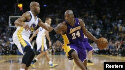 Pemain Los Angeles Lakers Kobe Bryant (kanan) menggiring bola basket, dijaga oleh Jarrett Jack dari Golden State Warriors pada pertandingan NBA Desember 2012. (Reuters/Stephen Lam)
