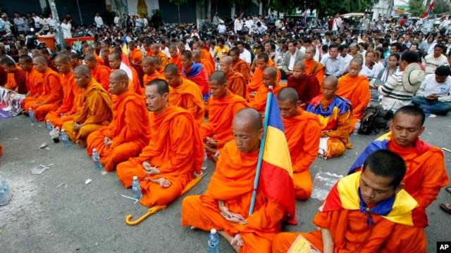 Các nhà sư Campuchia và những người biểu tình ngồi thiền 5 phút trong một cuộc biểu tình tại một con phố bị chặn gần Đại sứ quán Việt Nam ở Phnom Penh, 13/8/2014.