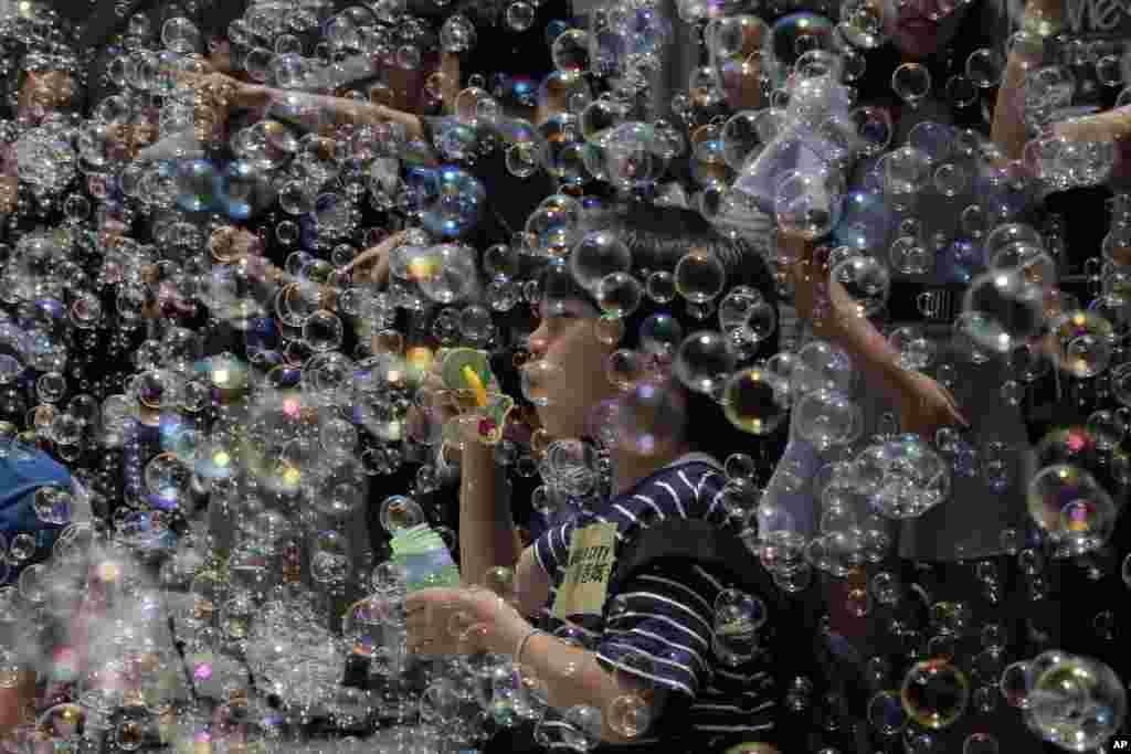 بازی کردن پسر بچه ای با حبابها در نمایشگاه «پرواز حبابها» از یک هنرمند ژاپنی در هنگ کنک.