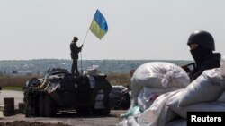 FILE - A Ukrainian soldier raises a Ukrainian flag on top of an armored personnel carrier at a checkpoint near the town of Slovyansk in eastern Ukraine.