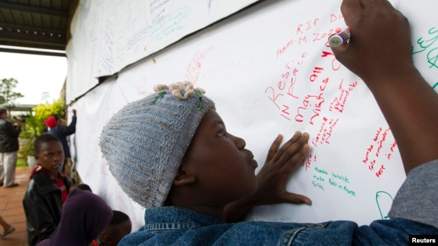 A child writes a note to former South African President Nelson Mandela on a banner at the Nelson Mandela Museum in Qunu, Dec. 12, 2013.