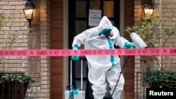 Član tima za rad sa opasnim materijalima dezinfikuje ulaz u stan medicinske sestre Teksaške prezbiterijanske bolnice, koja se zarazila ebolom u Dalasu.