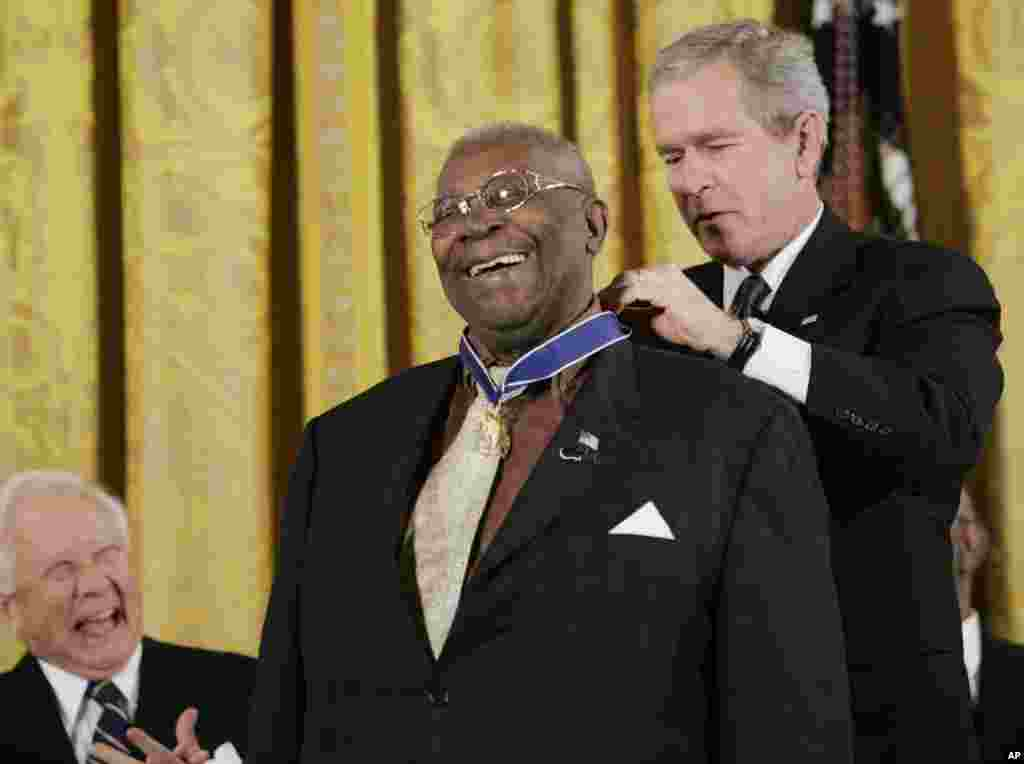 President Bush, right, bestows the Presidential Medal of Freedom to Blues Musician B.B. King, center, during a ceremony in the East Room of the White House in Washington, Dec. 15, 2006.