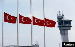 Turkish flags, with the control tower in the background, fly at half mast at the country's largest airport, Istanbul Ataturk, following yesterday's blast in Istanbul, Turkey, June 29, 2016.