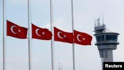 ທຸງຊາດຂອງເທີກີ ຖືກລົດລົງເຄິ່ງເສົາ ໂດຍມີອາຄານ ຫໍຄວບຄຸມ ຢູ່ດ້ານຫຼັງ, ພັດປິວຢູ່ທີ່ສະໜາມບິນ ທີ່ໃຫຍ່ Istanbul Atatur ທີ່ສຸດຂອງປະເທດ ຫຼັງຈາກທີ່ ຖືກໂຈມຕີດ້ວຍລະເບີດສະຫຼະຊີບ ເມື່ອມື້ວານນີ້, ວັນທີ 29 ມິຖຸນາ 2016.