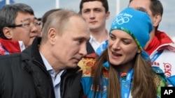 Le président russe Vladimir Putin parle avec la maire du village olympique Elena Isinbaeva lors des Jeux d'hiver de Sochi, Russie, le 5 février 2014.
