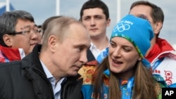 Le président russe Vladimir Poutine, avant les J.O de Sochi 2014 (Russie), avec Yelena Isinbayeva, la double championne olympique de saut à la perche, privée de Rio 2016 dans le cadre de la suspension de la Fédération russe d'athlétisme.