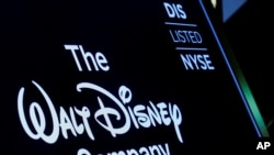 FILE - A screen shows the logo and a ticker symbol for The Walt Disney Company on the floor of the New York Stock Exchange in New York, Dec. 14, 2017.