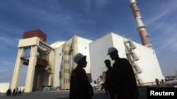 Pekerja Iran di depan pembangkit listrik tenaga nuklir Bushehr, sekitar 1.200 kilometer dari selatan Teheran.