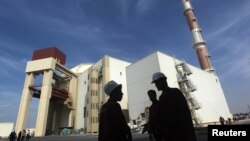 FILE - Iranian workers stand in front of the Bushehr nuclear power plant, about 1,200 km (746 miles) south of Tehran.
