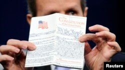 FILE - U.S. Treasury Secretary Timothy Geithner holds up a copy of the U.S. Constitution before reading a passage from the 14th Amendment at the Newseum in Washington, May 25, 2011.