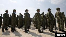 FILE - Soldiers of Japan's Self Defence Force stand at attention during the opening ceremony of a military base on the island of Yonaguni in the Okinawa prefecture, March 28, 2016.