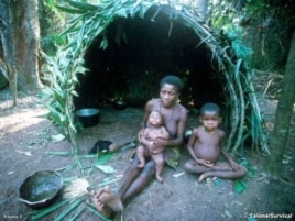 A Pygmy woman with her children outside their hut in a rainforest