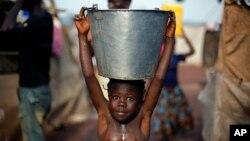 Seorang anak yang membawa ember berisi air berjalan di tengah lumpur menyusul badai yang menyerang kamp pengungsi di bandar udara Bangui, Republik Afrika Tengah (2/2). (AP/Jerome Delay)