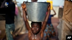 A child carrying a bucket full of water walks in mud after a storm in the airport camp in Bangui, Central African Republic, Sunday Feb. 2, 2014. Over 130,000 have seemed refuge outside the airport, living in dismal conditions, as fighting between Muslim