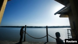 FILE - A man and his son are seen at a jetty during a search and rescue in Kuala Langat outside Kuala Lumpur, off Malaysia's western coast, June 18, 2014.
