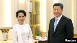 លោកប្រធានាធិបតី Xi Jinping និងលោកស្រី អង់សាន ស៊ូជី ឈរថតរូបក្នុងកិច្ចប្រជុំរបស់ពួកគេនៅវិមាន Great Hall of the People នៅក្នុងក្រុងប៉េកាំង ប្រទេសចិន កាលពីថ្ងៃទី១១ ខែមិថុនា ឆ្នាំ២០១៥។