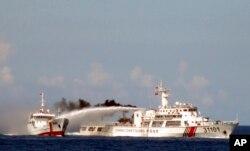 越南海岸警卫队公布的照片显示一艘中国海警船(右)在越南海岸外用水炮攻击一艘越南船(资料照片)