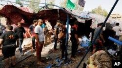 Warga Irak berkumpul di lokasi serangan bunuh diri di distrik al-Shaab, Baghdad, Irak hari Sabtu (15/10).