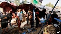 Iračani okupljeni na pijaci gde se dogodio samoubilački napad u distriktu al-Šab u Bagdadu