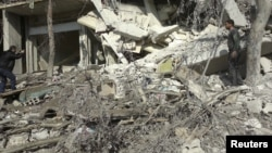 Một nhà hoạt động chụp hình một tòa nhà bị sụp đổ sau khi trúng phi đạn của máy bay chiến đấu của Lực lương Không quân Syria, 27/10/12
