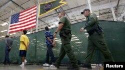 Menores inmigrantes detenidos son llevados a hacer llamadas telefónicas a sus parientes en un centro de procesamiento en Nogales, Arizona.