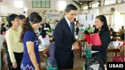 USAID Administrator Rajiv Shah (center) visits workers at a health supply warehouse in Rangoon.