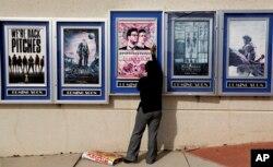 소니 영화사에 대한 북한의 사이버 공격으로 영화 '인터뷰' 개봉이 전격 취소된 가운데, 지난 2014년 12월 미국 아틀란타의 한 극장에서 영화 '인터뷰' 포스터를 내리고 있다.