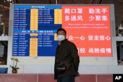 In this March 12, 2020, photo, a man wearing a mask stands near a display board at the Capital International Airport terminal 3 in Beijing.