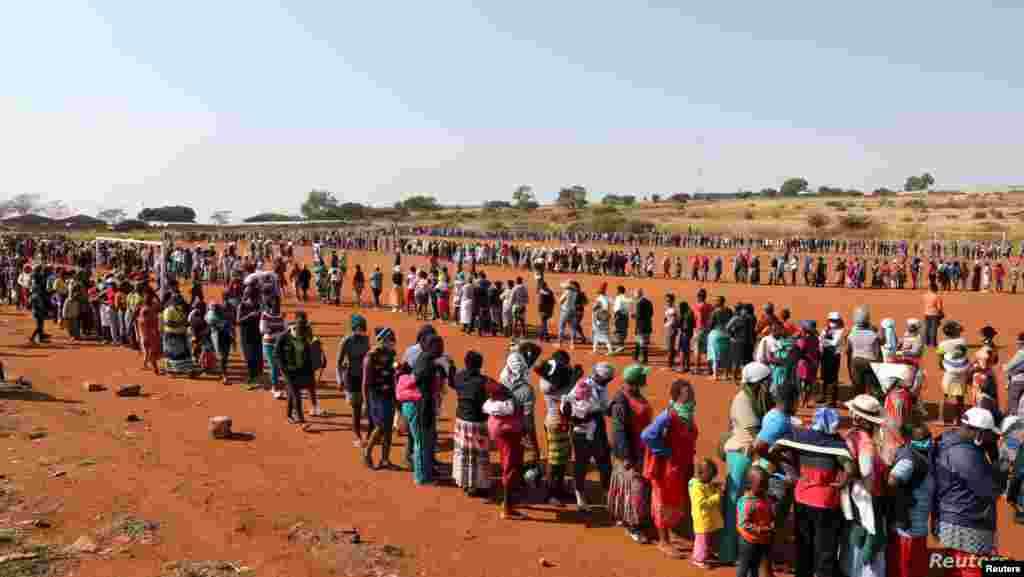 남아프리카공화국 프레토리아 인근에 위치한 임시 거주촌에서 주민들이 신종 코로나바이러스 감염증(COVID-19) 대응 일환으로 배급되는 무료 음식을 받기 위해 줄 서 있다.