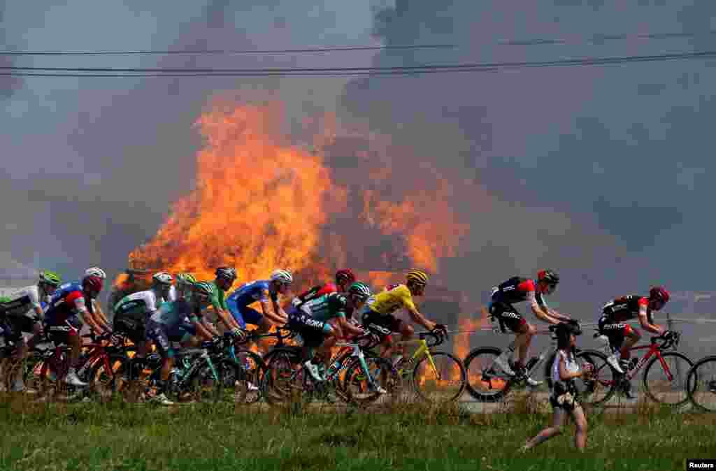 Tour de France'ta bisikletçiler yanan saman balyalarının önünden geçiyor.