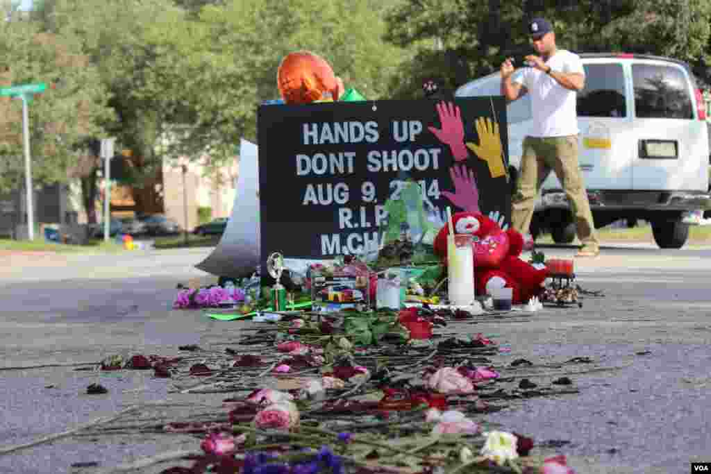 A tribute of flowers and signs are seen at the site that teenager Michael Brown was shot and killed by a police officer, Ferguson, Missouri, Aug. 24, 2014. (Gesell Tobias, VOA)