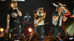 Nelly, center, and Brian Kelley, left, and Tyler Hubbard, of musical group Florida Georgia Line, perform at ACM Presents: Tim McGraw's Superstar Summer Night at the MGM Grand Garden Arena, April 8, 2013, in Las Vegas.