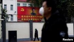 戴着口罩的行人走过上海街头习近平的画像。(2020年2月10日)