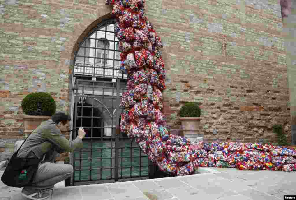 "A visitor takes a picture of part of an installation called ""The Garbage Patch State"" by Italian artist Maria Cristina Finucci during the 55th La Biennale of Venice, Italy."