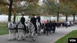 Một toán ngựa kéo quan tài phủ cờ được đặt trên một chiếc xe đến địa điểm huyệt mộ
