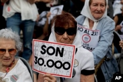 """FILE - Mothers of """"Plaza de Mayo"""" member Tati Almeida holds a sign that reads in Spanish """"They are 30,000,"""" referring to those killed by the Argentine dictatorship, as she listens to the verdicts for the accused in a human rights trial, Nov. 29, 2017."""