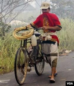 Seorang petani menutup hidungnya dari asap kebakaran hutan di Rokan Hilir, Riau tahun 2005 silam. Berbagai organisasi pemuda menilai kebijakan pemerintah tidak berpihak pada petani (foto: dok).