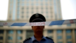 A police officer stands guard at the entrance to the Jinan Intermediate People's Court. August 24, 2013.