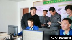 North Korean leader Kim Jong-un, left, gives field guidance at the Wonsan Shoes Factory in this undated photo released by North Korea's Korean Central News Agency (KCNA) in Pyongyang, Nov. 27, 2015.