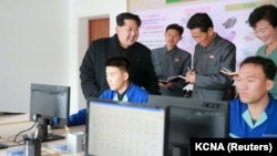 FILE - North Korean leader Kim Jong-un (l) gives field guidance at the Wonsan Shoe Factory in this undated photo released by North Korea's Korean Central News Agency (KCNA) in Pyongyang, Nov. 27, 2015.