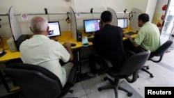 FILE - People surf the Internet at an Internet cafe in Baghdad, Nov. 11, 2012.