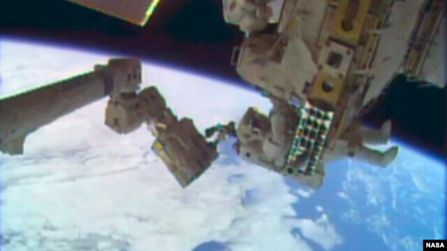 Astronauts Rick Mastracchio and Michael Hopkins (not shown) work to repair an external cooling line on the International Space Station, 260 miles above Earth, Dec. 24, 2013.