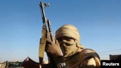 A soldier from the Tuareg rebel group MNLA holds an AK-47 in the northeastern town of Kidal February 4, 2013. The agreement calls for an immediate cessation of hostilities and the return of Malian troops and civil administration officials to Kidal.