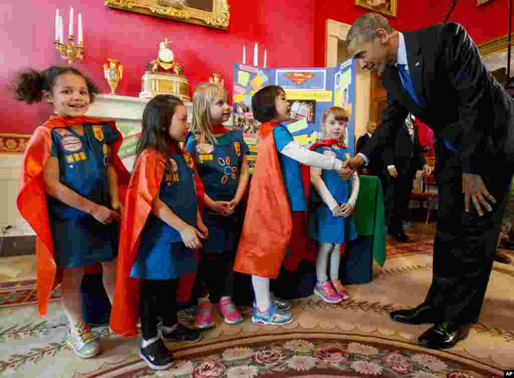 Dressed in super hero capes, six-year-old Girl Scouts, from left, Alicia Cutter, Addy O'Neal, Emery Dodson, Karissa Cheng, and Emily Bergenroth, of Tulsa, Oklahoma, meet with President Barack Obama before showing him their project during his tour of the White House Science Fair in Washington. The girls used Lego pieces and designed a battery-powered page turner to help people who are paralyzed or have arthritis.