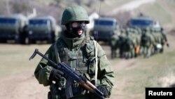 Một người đàn ông có vũ trang, được cho là một binh lính Nga, đứng bảo vệ bên ngoài căn cứ quân sự Perevalnoye, gần thành phố Simferopol, 21 tháng 3 năm 2014.