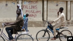 """FILE - Two boys ride their bicycles past a sign reading """"Stop killing Muslims Army"""" on a wall in Kano, Nigeria, April 8, 2016."""