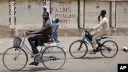 "Two boys ride their bicycles past a sign reading ""Stop killing Muslims Army"" on a wall in Kano, Nigeria, April 8, 2016. Nigeria's Kaduna state government has secretly buried hundreds of minority Shi'ite Muslims in a mass grave."